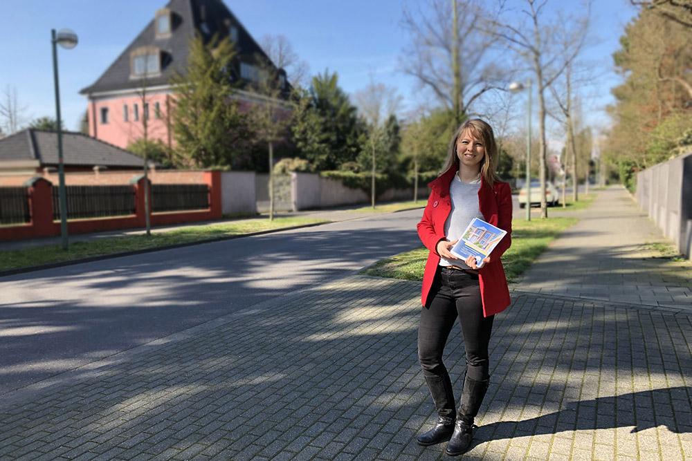 Maklerin verteilt Flyer in der Gartenstadt in Meerbusch für eine Villa in Düsseldorf-Ludenberg/Hubbelrath